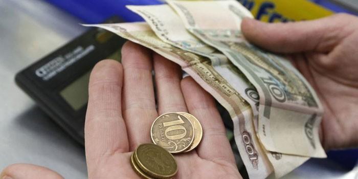 Купюры и монеты в руках