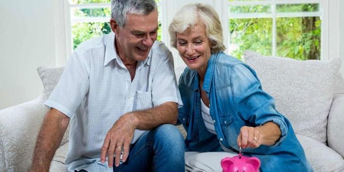 Пожилые мужчина и женщина кладут монету в копилку