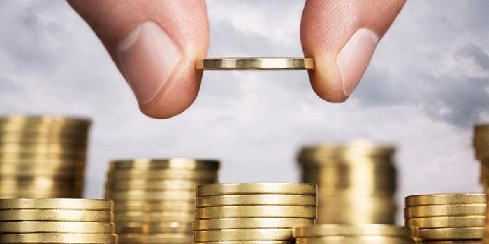 Человек складывает монеты столбиками