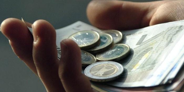 Купюры и монеты в руке