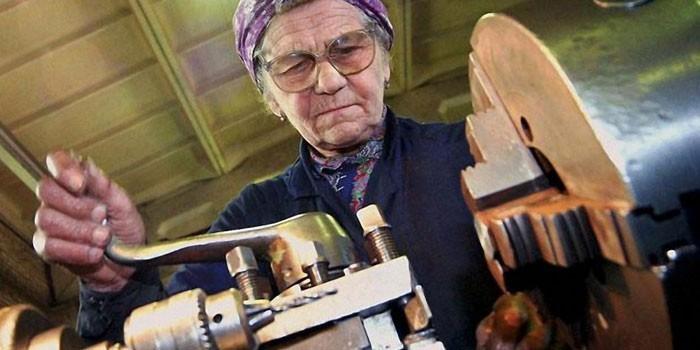 Пожилая женщина работает на станке