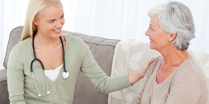 Пожилая женщина беседует с медработником