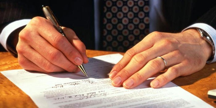 Мужчина подписывает бумаги
