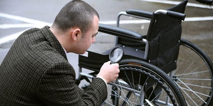 Мужчина осматривает инвалидную коляску