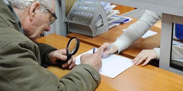 Пенсионер подписывает документ