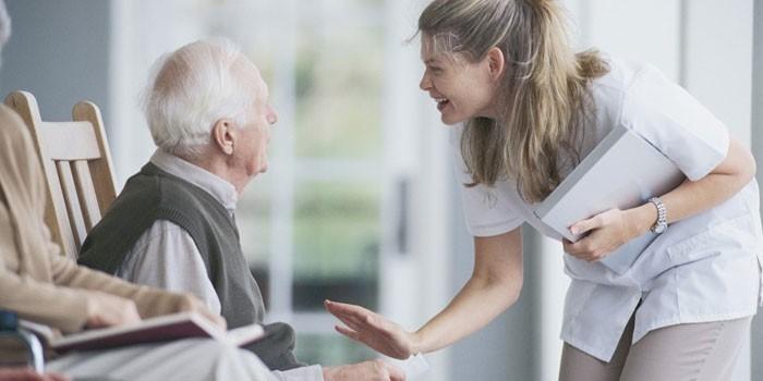 Медработник беседует с пожилым человеком