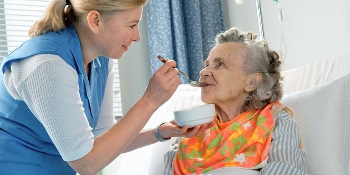 Медработник кормит пациентку