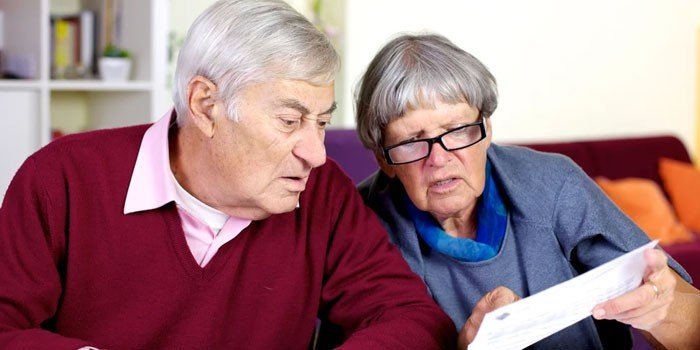 Пожилые люди изучают квитанцию
