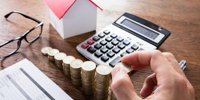 Калькулятор, домик и столбики из монет