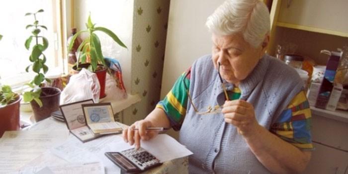 Пожилая женщина ведет подсчеты на калькуляторе