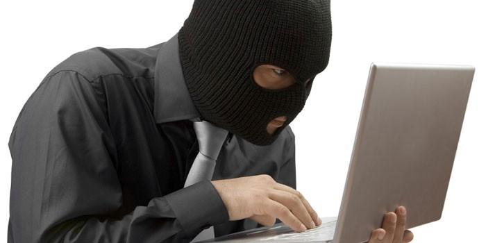 Человек в балаклаве за ноутбуком