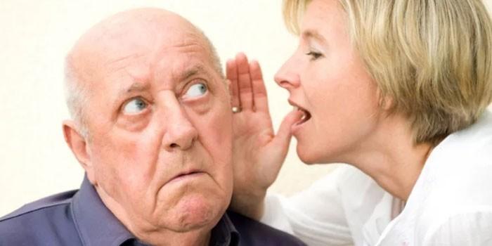 Женщина говорит мужчине на ухо