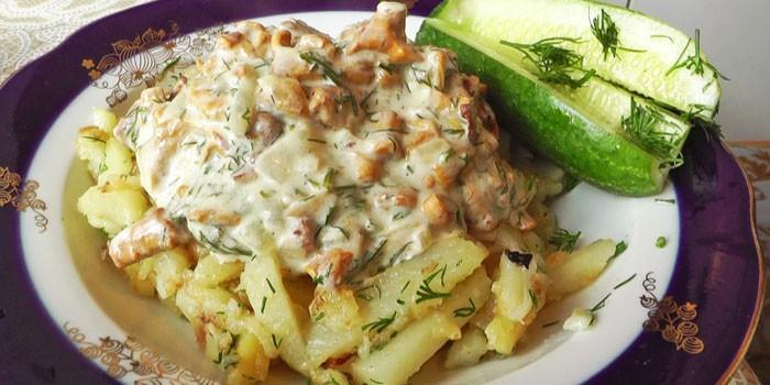 Жареная картошка с лисичками в сметанном соусе в тарелке
