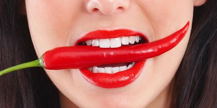 Горький перец в зубах девушки