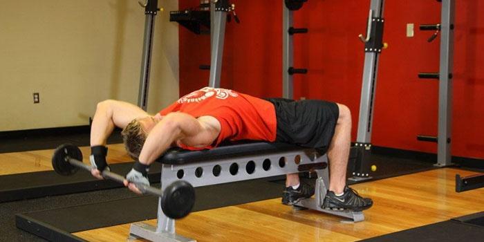 Мужчина делает упражнения со штангой для спины