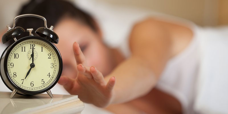 Девушка выключает будильник