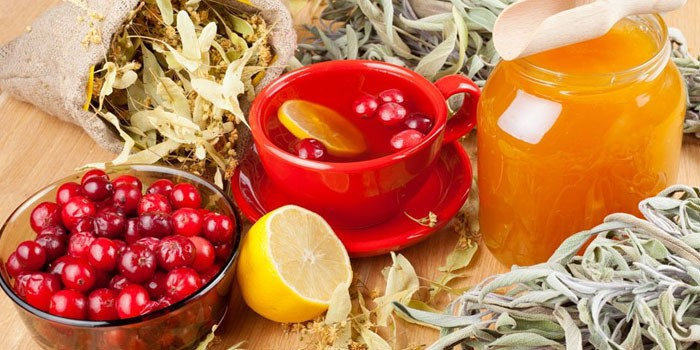 Ягоды, лимон, банка с медом, сухие лекарственные травы и ягодный чай в чашке