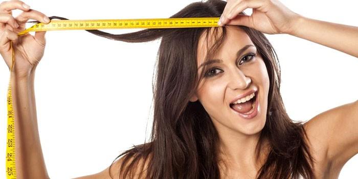 Девушка измеряет длину волос сантиметром