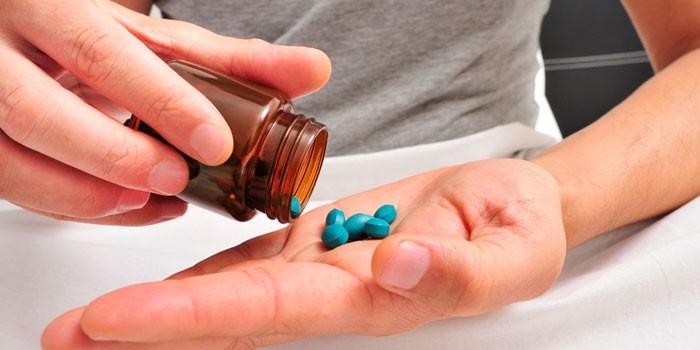 Мужчина с таблетками на ладони