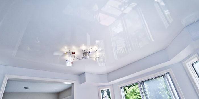 Глянцевый потолок белого цвета в интерьер гостиной