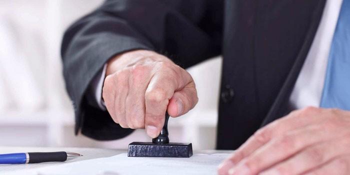 Мужчина ставит печать на документ