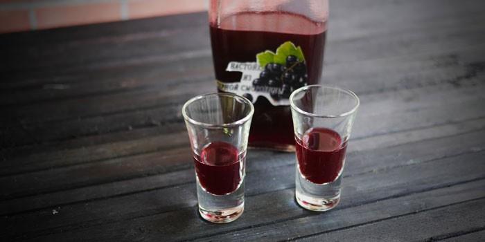 Наливка из черной смородины на водке в бутылке и рюмках