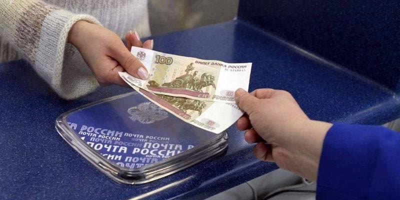 Девушка передает деньги работнику почты