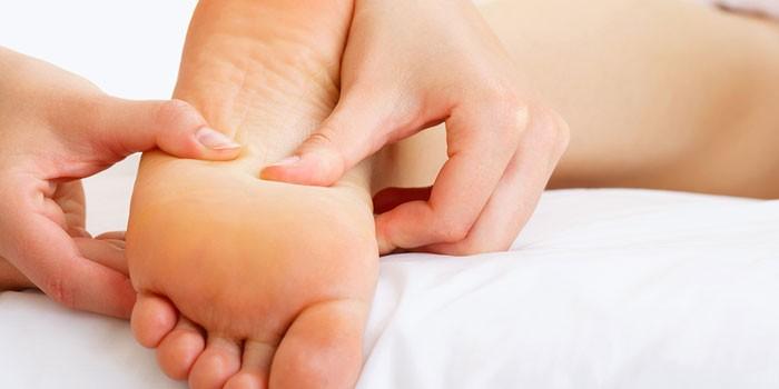 Женщине делают массаж стопы