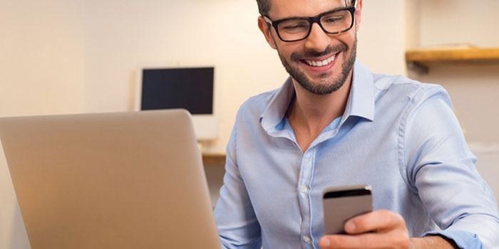 Мужчина со смартфоном и ноутбуком