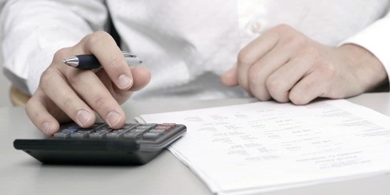 Мужчина ведет подсчеты на калькуляторе