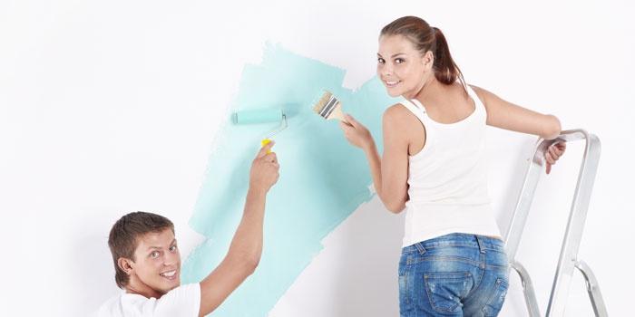 Парень и девушка красят стену