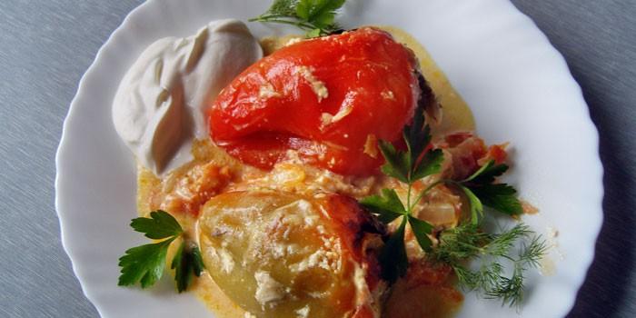 Готовые фаршированные перцы со сметаной и подливой на тарелке