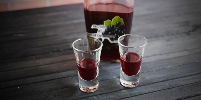 Вино из черной и красной смородины в рюмках и бутылке