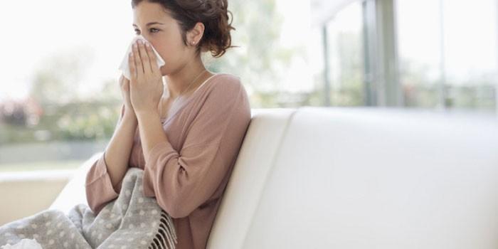 Девушка прикрывает нос платком
