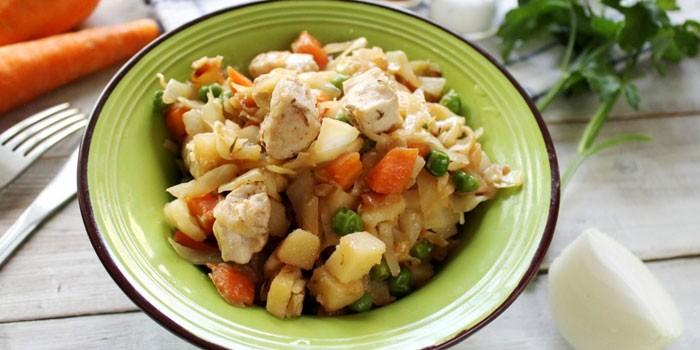 Овощное рагу с куриным мясом в тарелке