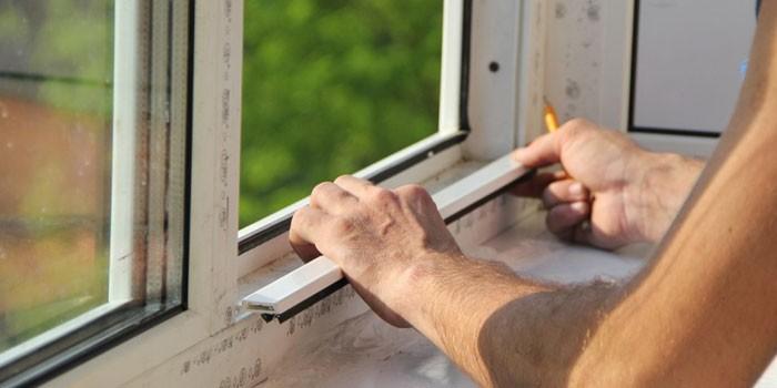 Мужчина утепляет пластиковое окно