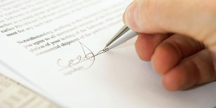 Человек подписывает документы