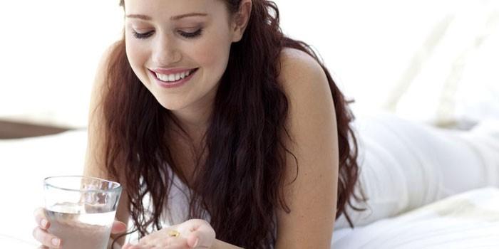 Девушка с таблетками и стаканом воды в руках