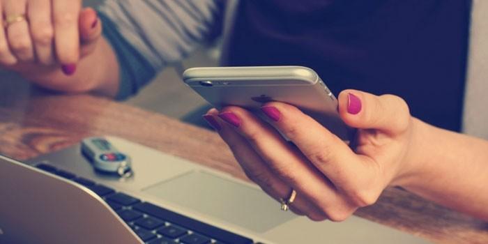 Девушка со смартфоном и ноутбуком