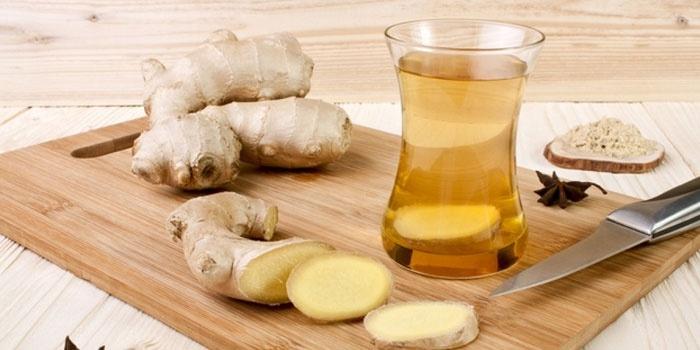 Корень имбиря на раделочной доске и имбирный чай в стакане