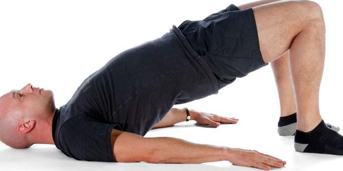Мужчина выполняет упражнение ягодичный мост