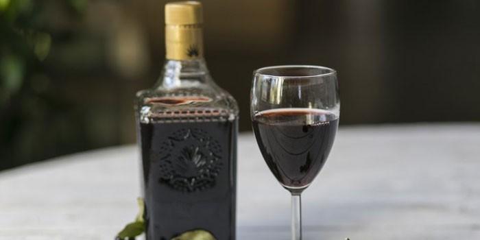 Черносмородиновое вино в бутылке и бокале