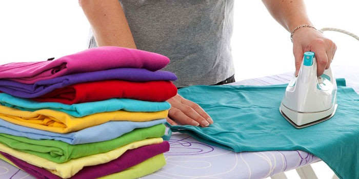 Девушка гладит утюгом футболки
