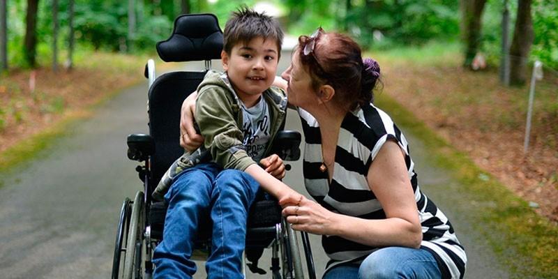 Мальчик в инвалидном кресле и женщина рядом