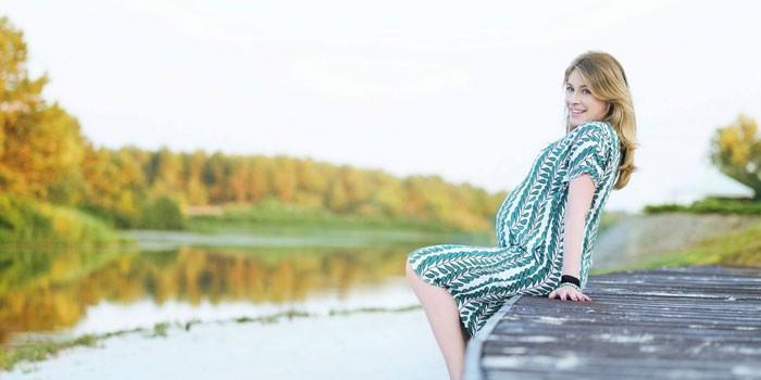 Беременная девушка сидит на причале