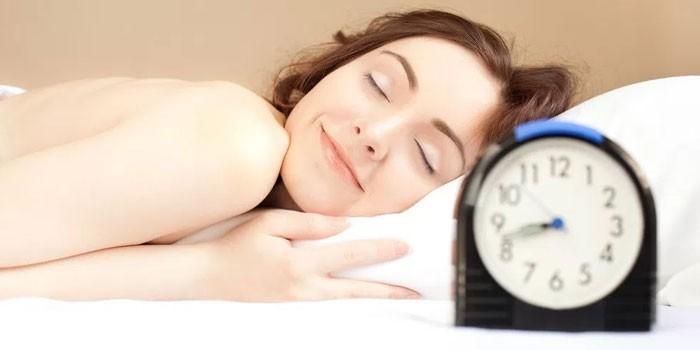 Девушка спит и часы у кровати