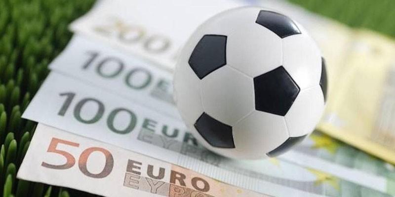 Денежные купюры и футбольный мяч