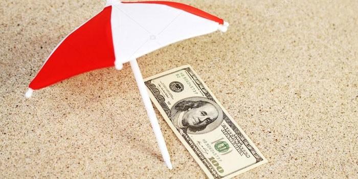 Деньги и зонтик на песке