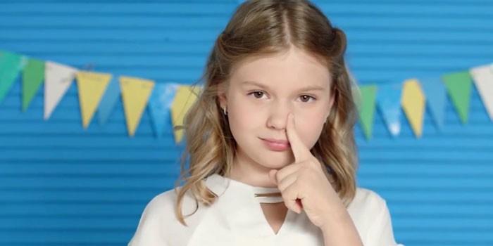 Девочка держит палец у носа