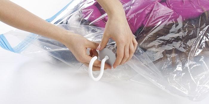 Девушка упаковывает вещи в вакуумный пакет с вешалкой